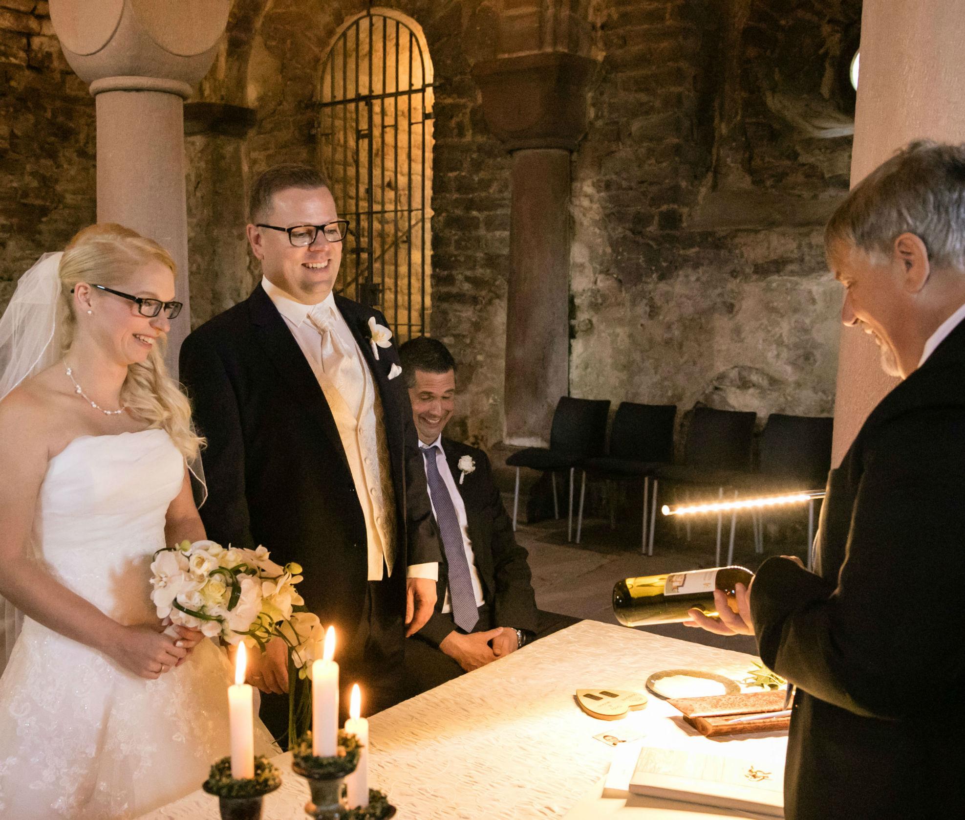 Standesbeamter überreicht dem frisch vermählten Brautpaar einen guten Tropfen Pfälzer Wein