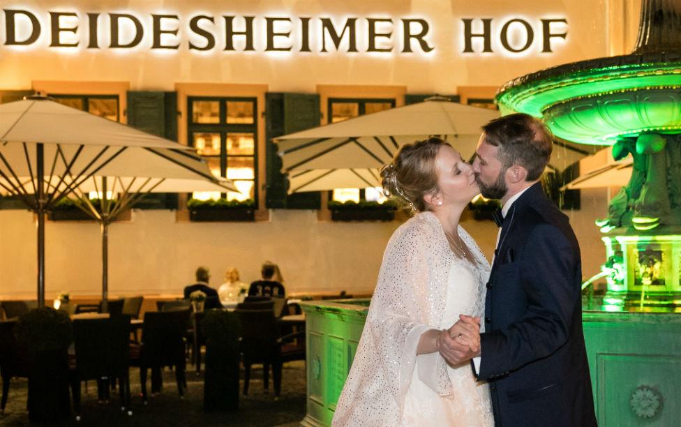 Brautpaarkuss am Abend vor dem beleuchteten Brunnen am Deidesheimer Hof